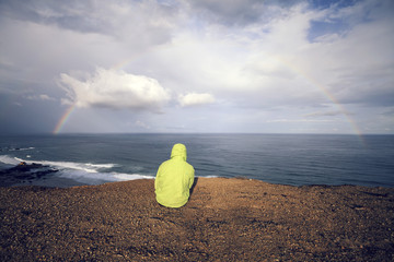 Portugal, Junger Mann sitzt am Strand Praia do Castelejo