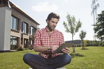 Deutschland, Nürnberg, Mann mit Tablet PC im Garten