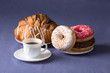 Cup of coffee with croissants and donuts