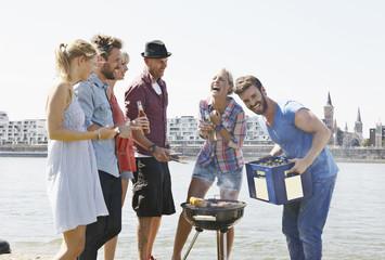 Deutschland, Köln, Männer und Frauen versammelen sich um Grill