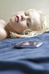 Deutschland, Kiel, Mädchen liegt auf dem Bett mit Smartphone