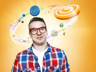 Lächelnder junger Mann, schauen auf fliegende Bonbons, Composite