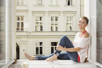 Deutschland, Berlin, Junge Frau sitzt am offenen Fenster