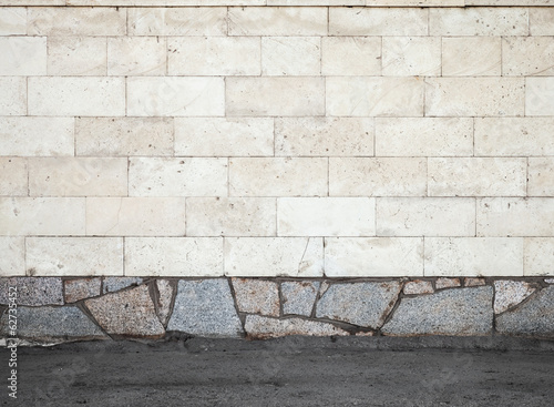 Urban background texture with stone wall and asphalt ground