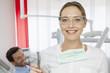 Deutschland, Zahnarzt mit Schutzbrille, Patienten im Hintergrund