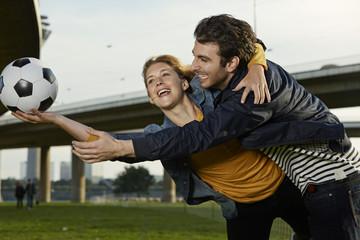 Deutschland, Düsseldorf, Junges Paar spielen Fußball