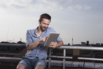 Deutschland, Berlin, Mann mit Tablet PC auf der Dachterrasse