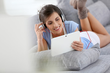 Smiling brunette girl listening to music relaxed on sofa