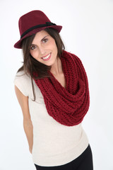 Cheerful trendy girl with maroon scarf and hat