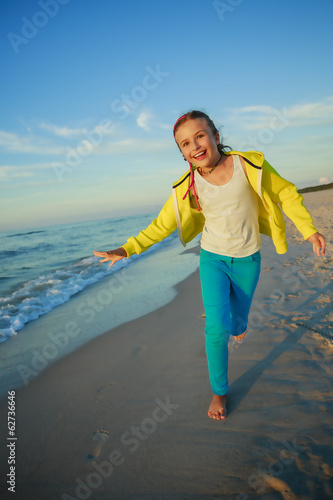 Summer joy - young girl playing on the beach
