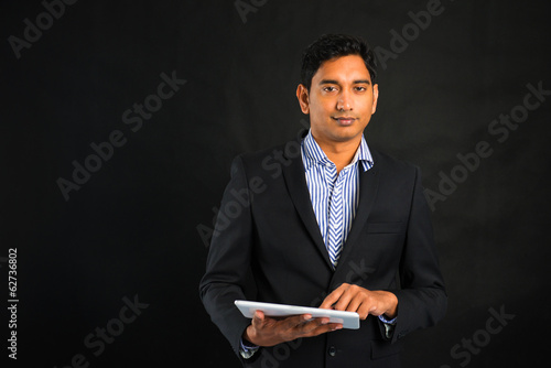 indian business male with tablet on dark background