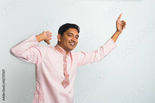 young indian male in traditional cloths celebrating bhangra