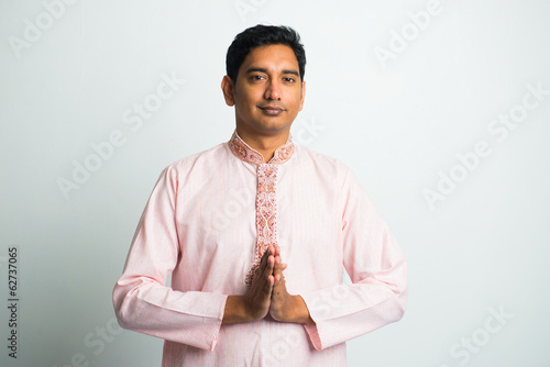 young indian male with  Pranamasana greetings sign on traditiona