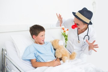 Doctor in clown costume entertaining ill boy in hospital