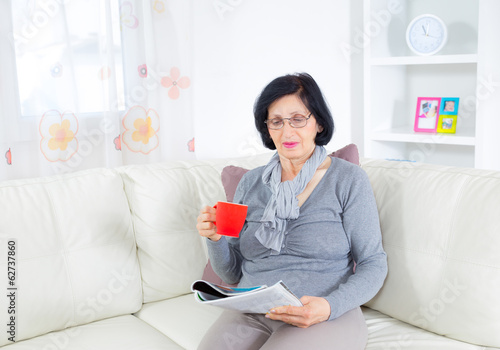 Grandmother enjoying a rest, reading magazine and drinking coffe