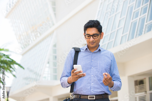confused looking indian business male on a phone with office bac
