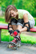 Girl going rollerblading sitting in bench putting on inline skat