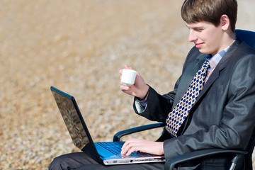 A man working on a computer outdoors.