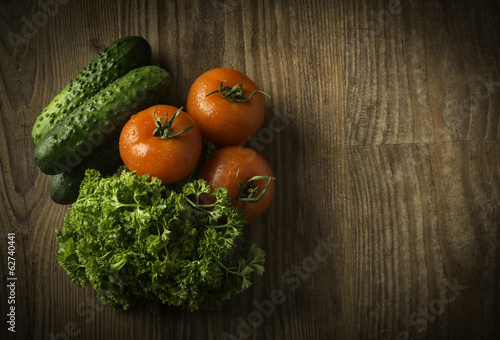 red tomatoes and a cucumber on green verdure
