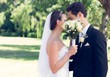 Couple kissing behind bouquet in garden