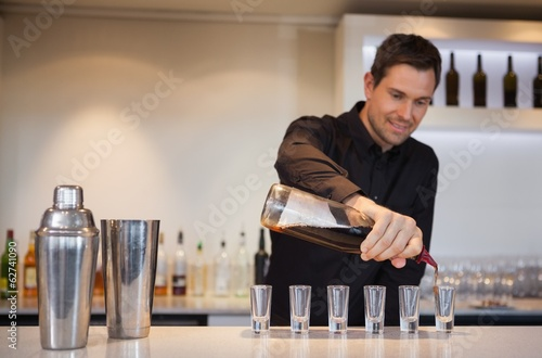 Happy bartender pouring cocktail into shot glasses