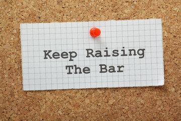 The phrase Keep Raising the Bar on a piece of graph paper