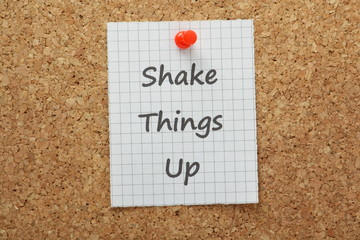 The phrase Shake Things Up on a cork notice board