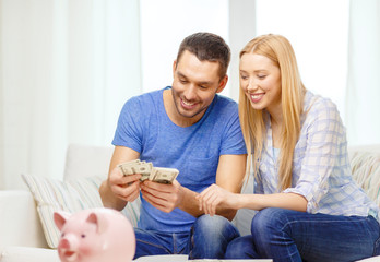smiling couple counting money at home