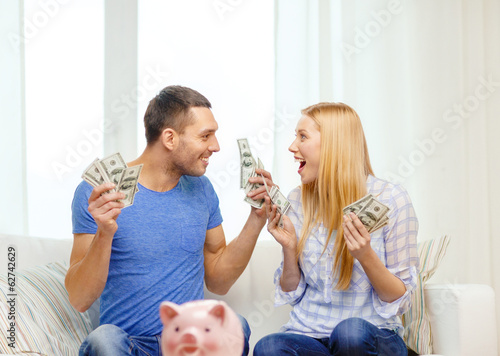 couple with money and piggybank ot table at home