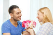 smiling man giving girfriens flowers at home