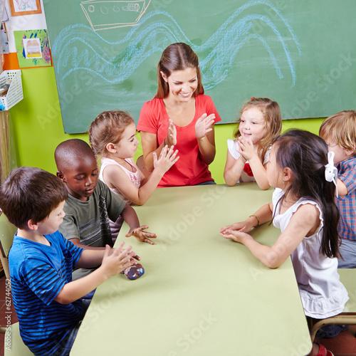 Kinder klatschen in Hände im Kindergarten