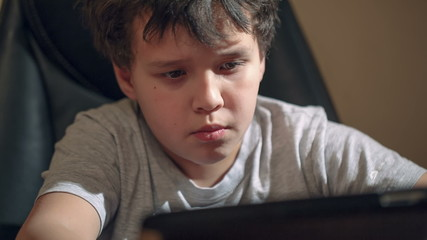 Kid with tablet PC at the table