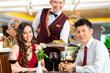 Chinese waiter serving dinner in elegant restaurant or Hotel