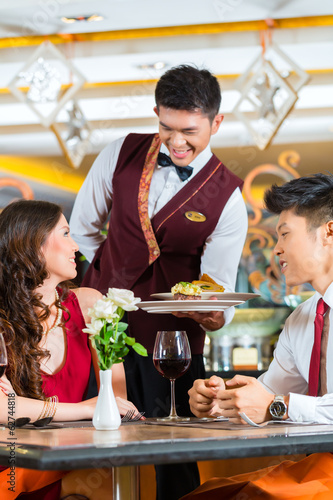 Chinese waiter serving dinner in elegant restaurant or Hotel