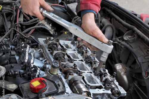 Mechanic fixing cylinder head with camshaft using socket wrench