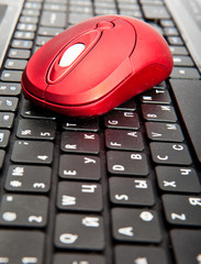 The red computer mouse on the black keyboard..