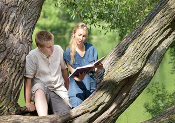 Young guy and girl with textbooks on the bank of lake