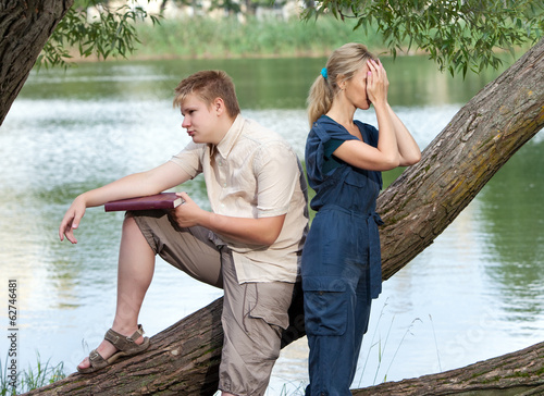 Young guy and girl on the nature near lake, quarrel