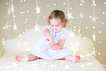 Adorable toddler girl playing with a toy on a white bedroom