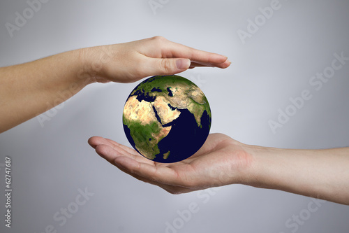 The Earth in a female and male hands