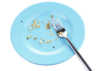 Plate with crumbs and used fork, close-up, on white background