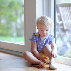 Cute toddler girl putting on her shoe sitting next to a window