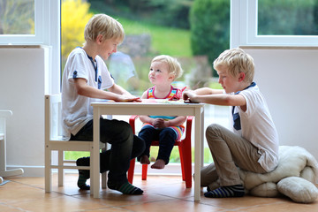 Two brothers and sister playing indoors making paper planes