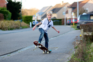 Happy active teenager boy learning to balance on skateboard