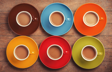 Six color cups of coffee on wooden table.