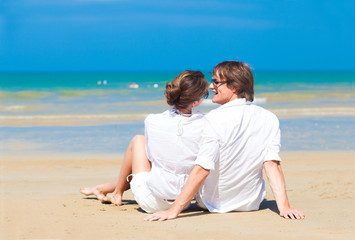 happy young couple in white clothes on beach