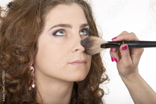 Make-up artist applying makeup at beautiful girl.