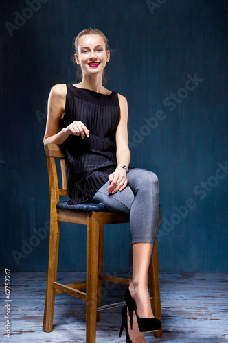 Beautiful young girl sitting on a wood chair