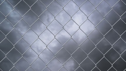 Chain link wire fence against cloudy sky time lapse