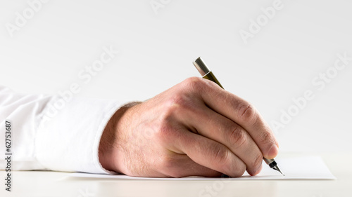 Man writing on a sheet of paper with a fountain pen